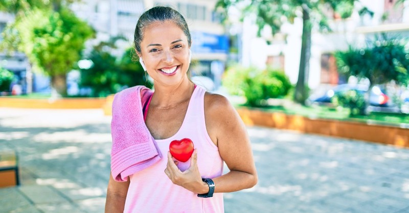 Older woman holding a toy heart after working out