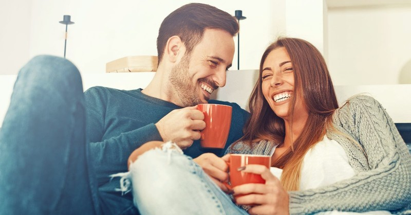 Husband and wife talking on a couch with coffee