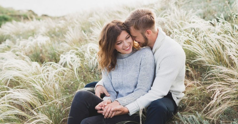 Engagement photos of a couple in a field