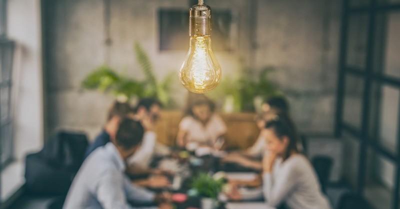 People meeting one light bulb