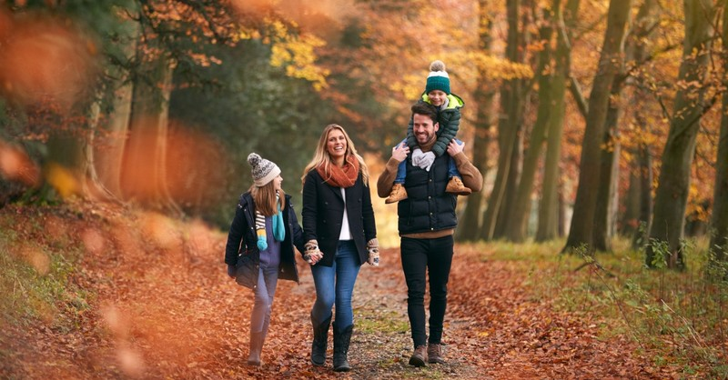 Family walking outside among the Autumn leaves