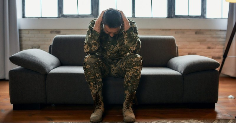 Soldier cradling his head on a couch