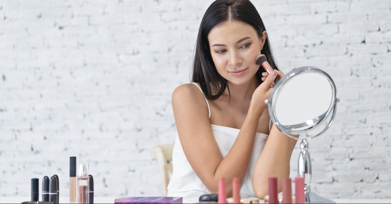 Woman vainly putting on makeup