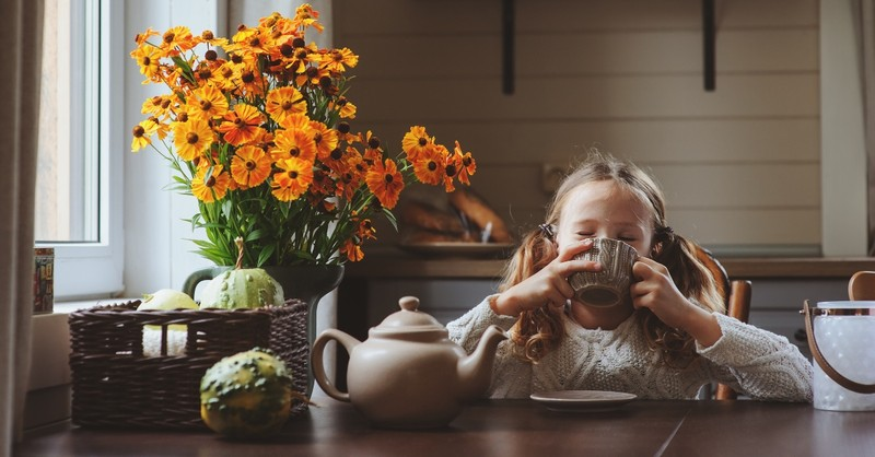 little girl with mug sitting at fall decorated table looking happy
