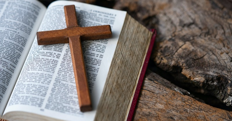 wooden cross laying on open Bible pages