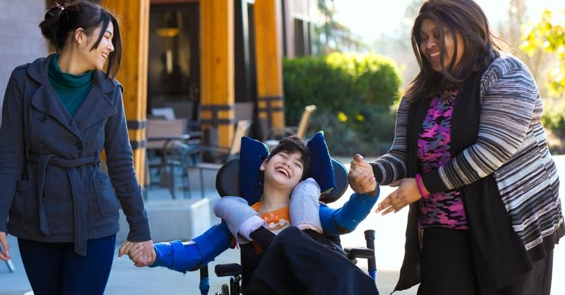 Women walking with a boy in a wheelchair