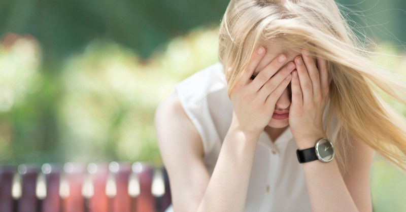 sad young woman sitting on park bench, signs of spiritual warfare and how to fight it