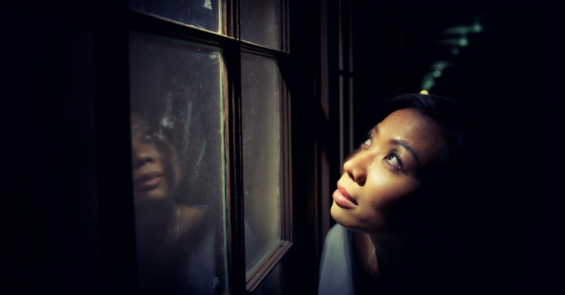 woman looking out window at sky