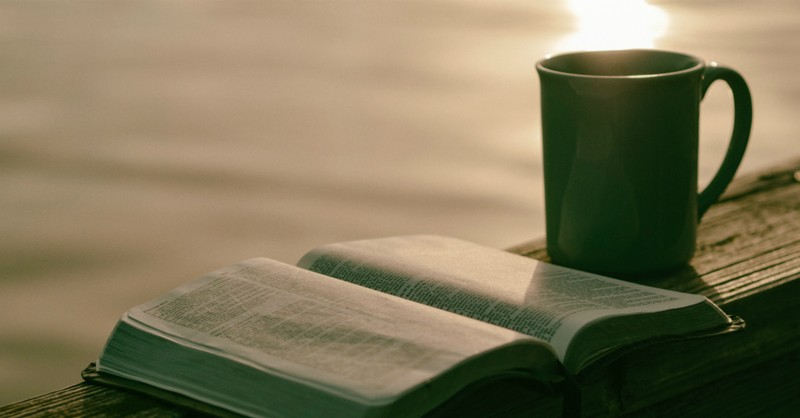 open Bible on deck railing with coffee overlooking water
