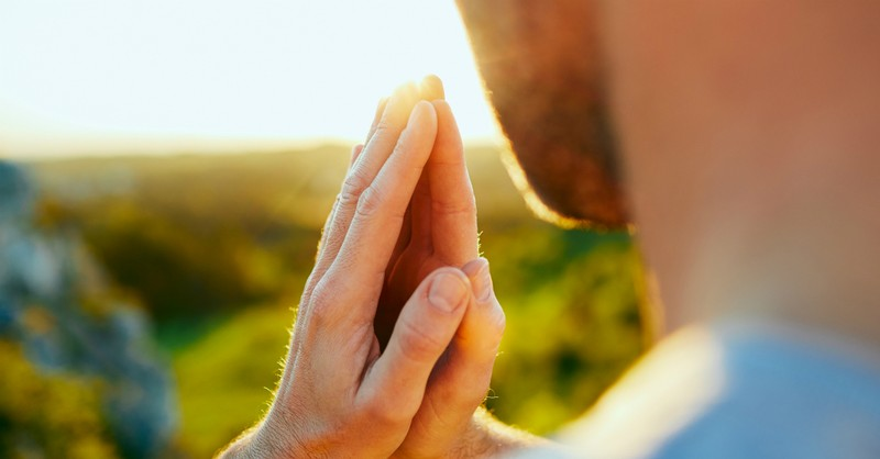 man with praying hands looking out toward sunrise over field
