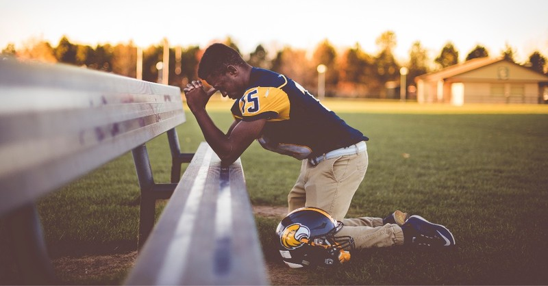 young football player praying by bench