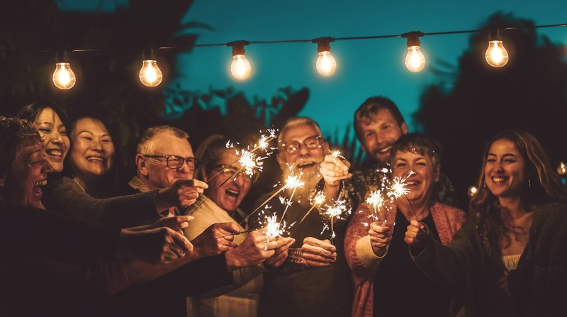 diverse group of adults celebrating with sparklers together at an outdoor party