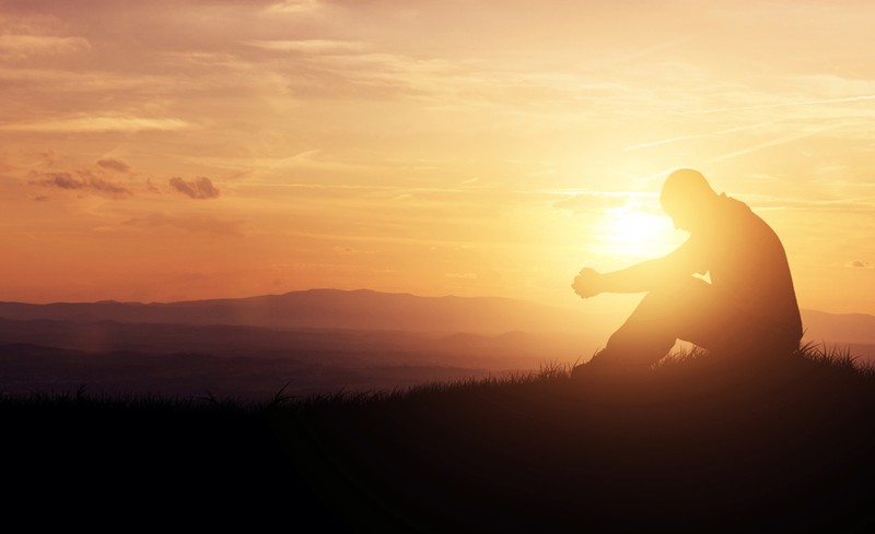 silhouette of man praying on a hill at sunrise