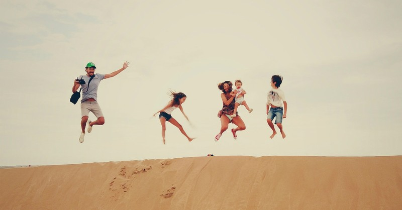 Family jumping together on a sand dune