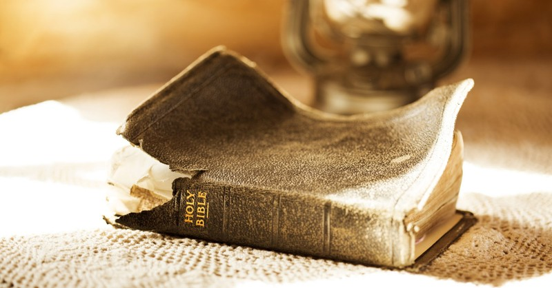old Bible on table by lamp