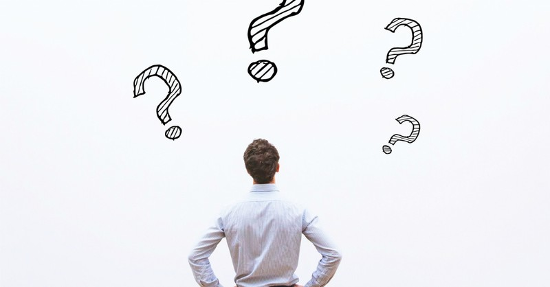 Man looking at a wall of question marks