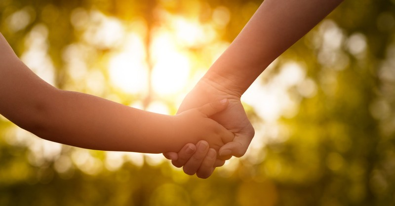 Adult holding hands with a child