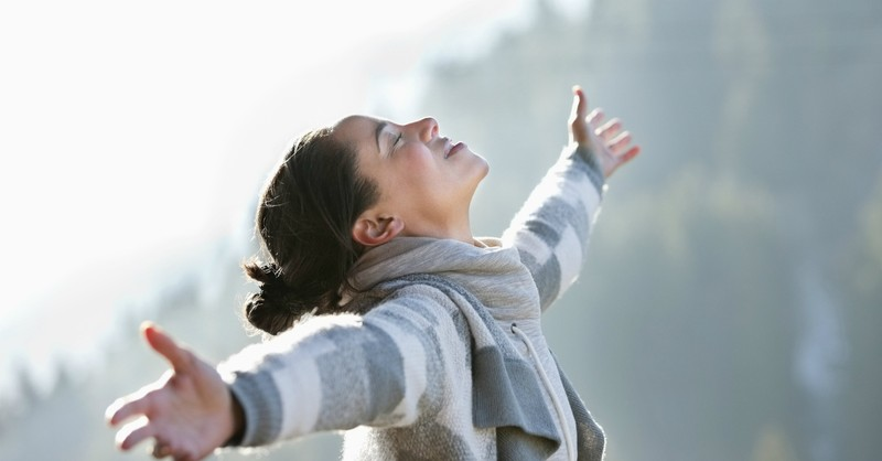 woman with arms wide in gratitude for God