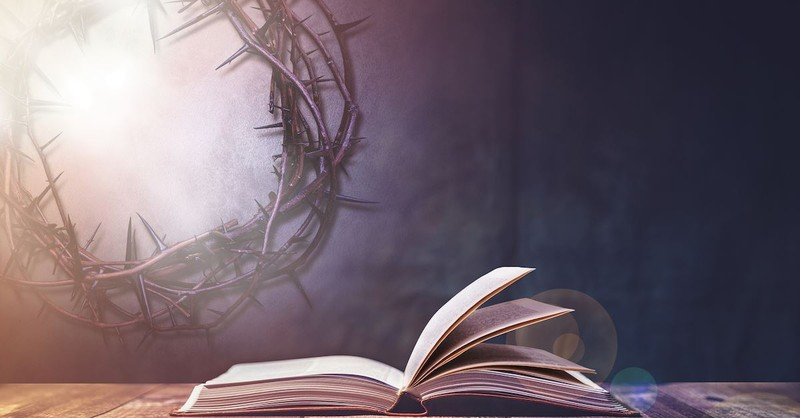 crown of thorns next to Bible with gray background