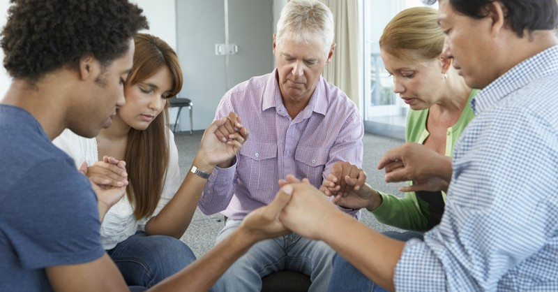 baby boomers and millennials in small group prayer