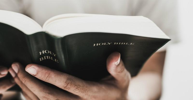 man holding Bible open