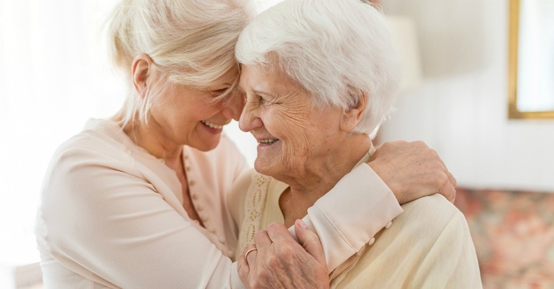 Two older women smiling and hugging