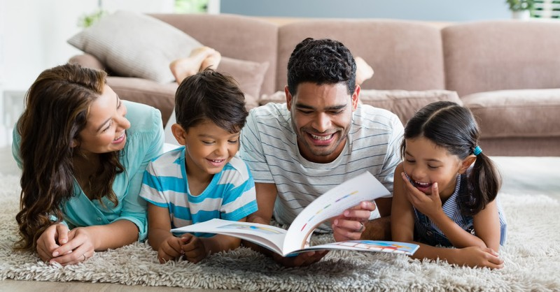 family reading book on the floor together, as for me and my house we will serve the Lord
