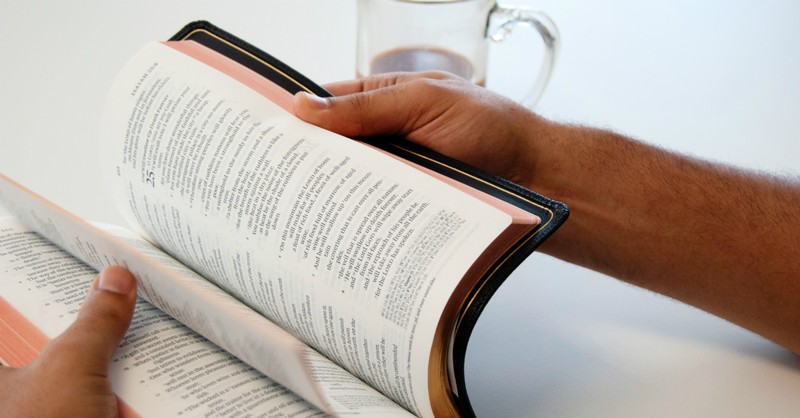 person flipping Bible open on Bible with coffee mug nearby
