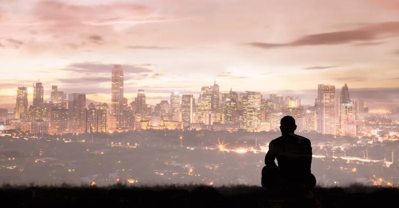 Homme assis seul en regardant une ville
