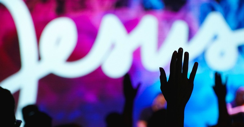 worship music on screen with silhouette of hands raised