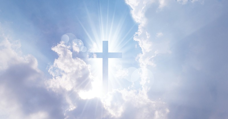silhouette of cross in bright blue sky and clouds