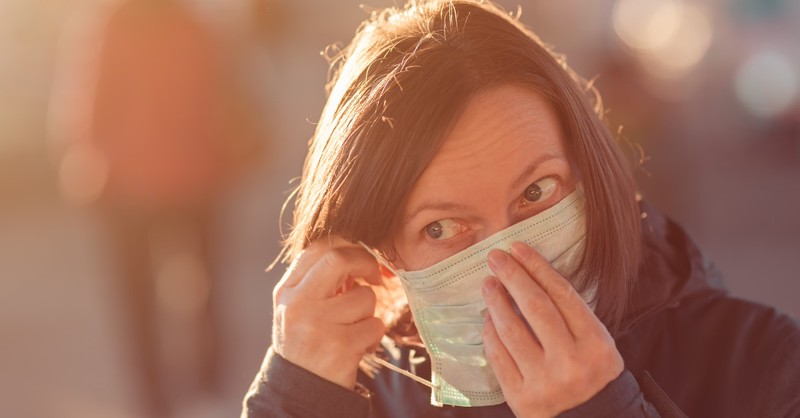 woman putting on face mask for COVID-19