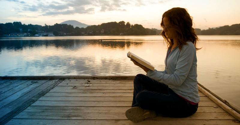 woman sitting on pier reading Bible