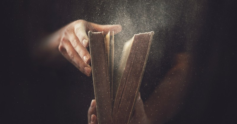 Man opening a dusty old Bible