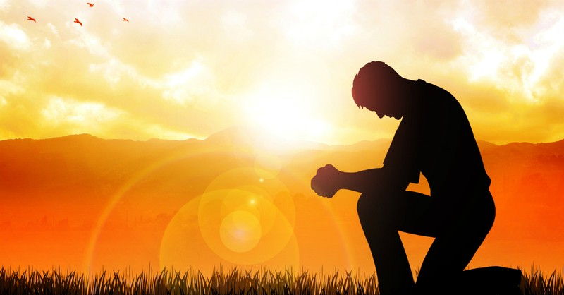 man kneeling at sunset in prayer