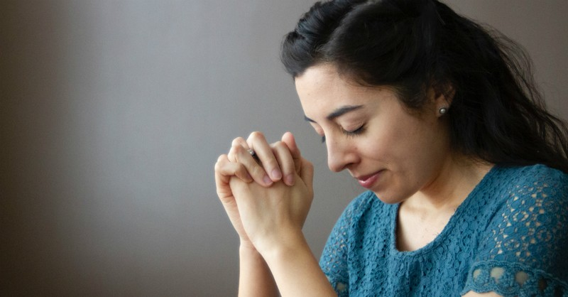 woman with head bowed praying, how to pray for someone