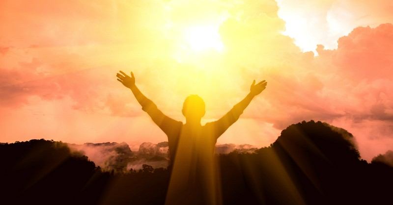 silhouette of person with outstretched arms toward sun