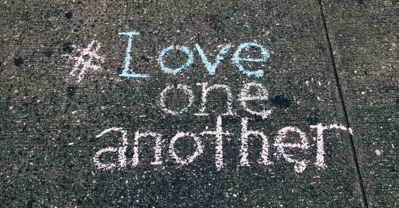 chalk written on road says 'love one another'