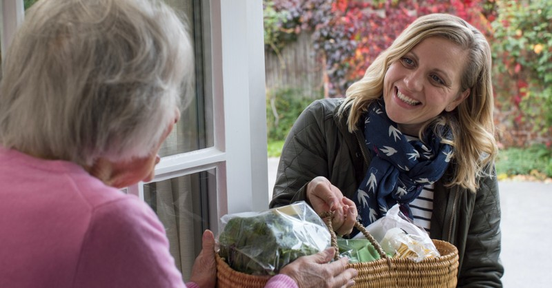 woman bringing groceries to a senior in need