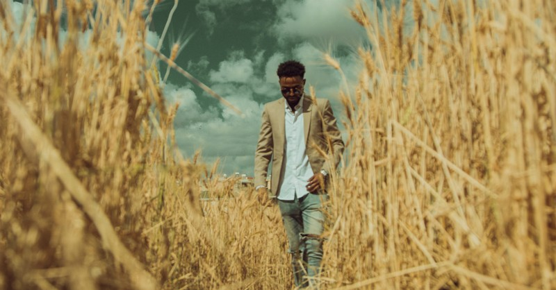 man walking through path in wheat field parable of wheat and tares