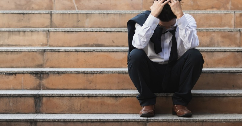 sad man in suit on steps