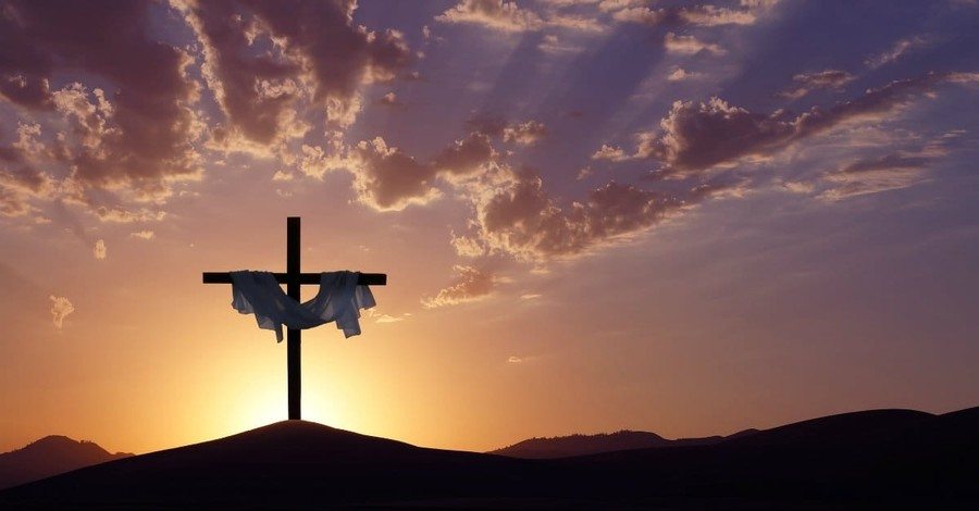 Cross with white fabric at sunset