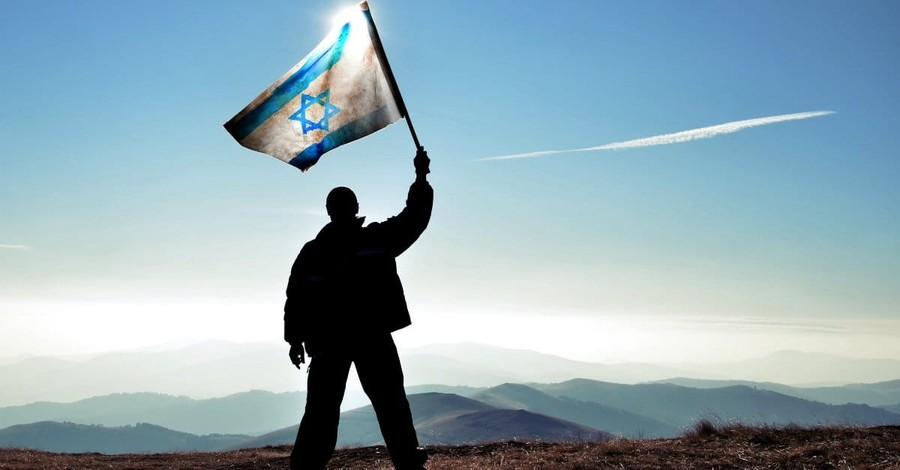 Silhouette of man waving Israel flag on mountain top