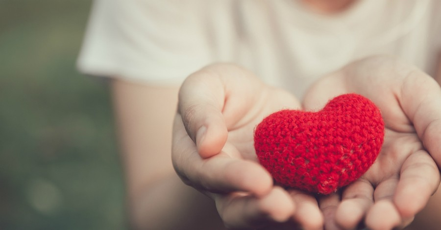 hands offering a red crocheted heart giving kindness