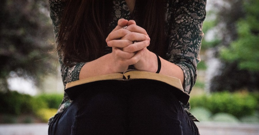 A woman praying, read this in case of a national emergency