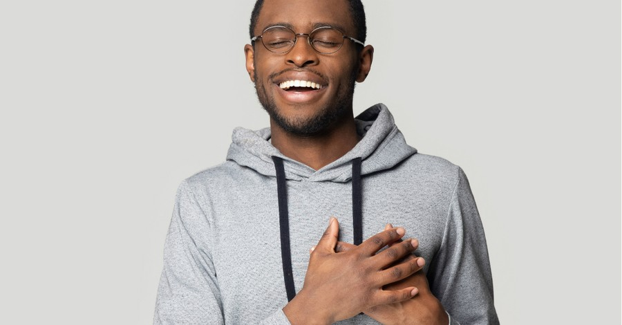 man smiling hands over heart peace and joy, Seeking transforming joy that transcends circumstances