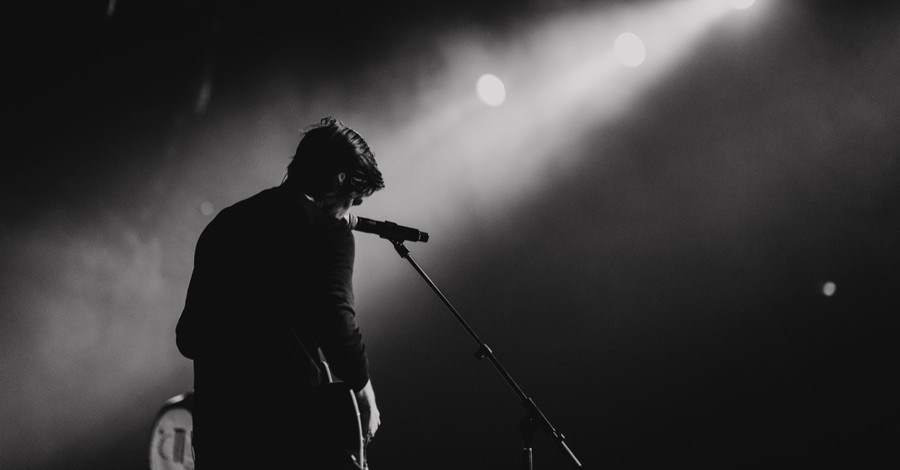 A solo singer on a stage, how covid-19 has impacted worship