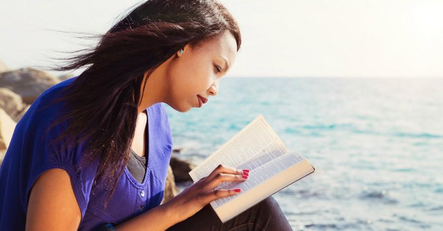 woman reading bible in purple shirt by ocean