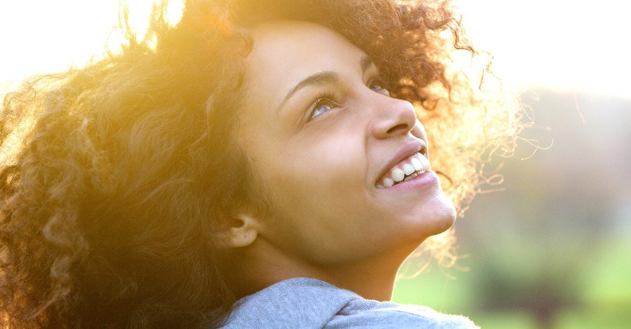 close up of woman looking up joyfully smiling, satisfied in god