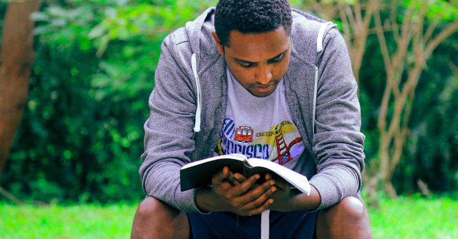 man reading bible outdoors